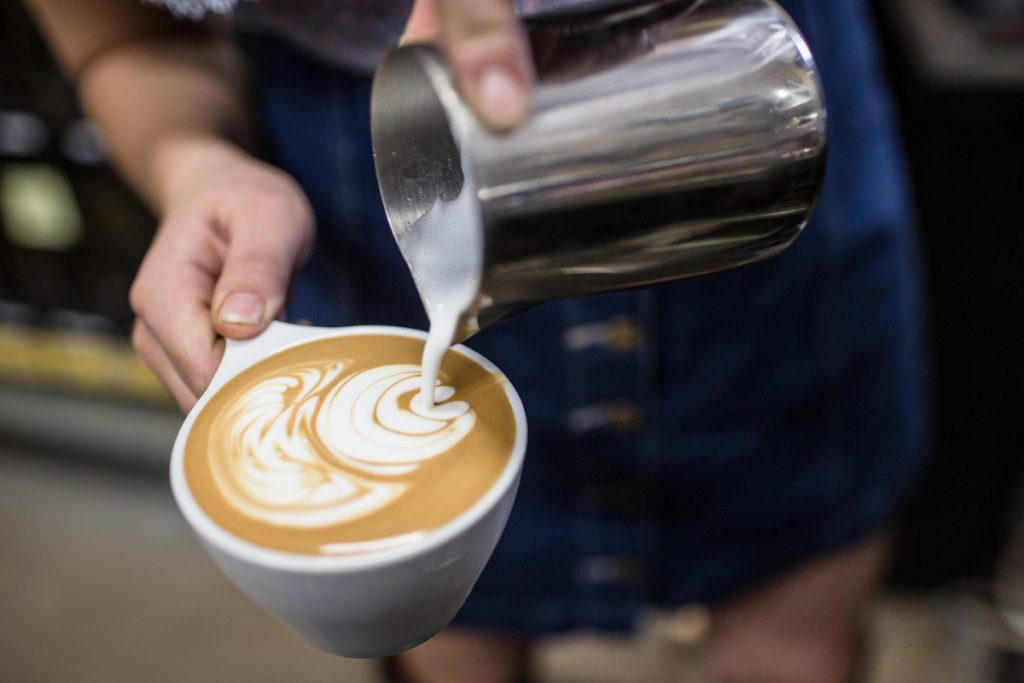 A barista pours milk into a coffee at Cafe Virtuoso in San Diego.