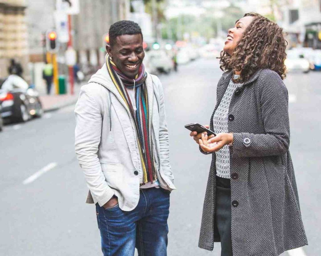 Man and woman laughing on the street while waiting for their ride
