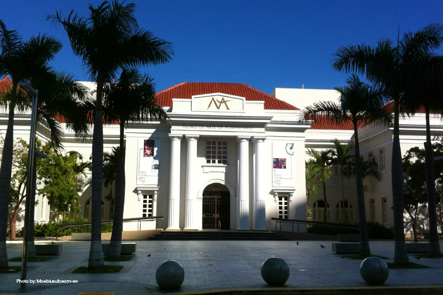 Front view of Museo de Arte of Puerto Rico surrounded by palm trees in a sunny day