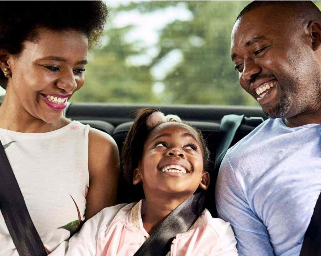 small girl and her parents inside their ride